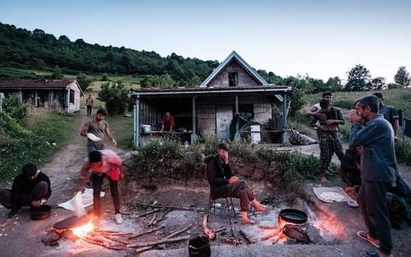 ボスニア・ヘルツェゴビナ北西部、ビハチの町。クロアチアに渡る直前、屋外キッチンで調理するパキスタンからの移民たち(PHOTOGRAPH BY ZIYAH GAFIC)