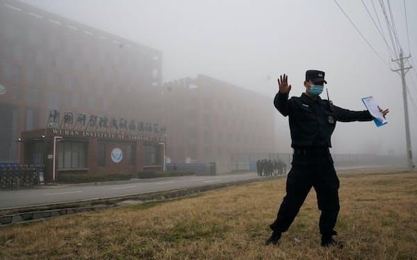 2021年2月3日、コロナウイルスの起源を調査するため、世界保健機関のチームが武漢ウイルス学研究所に到着した後、記者に近づかないよう指示する警備員(PHOTOGRAPH BY NG HAN GUAN, AP)