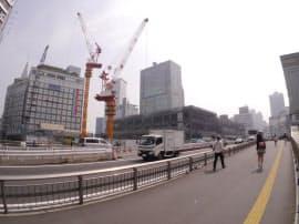 甲州街道に面したJRの線路上で、駅前広場やバス乗り場などを組み合わせた4階建ての施設を整備する工事が進む。写真右手に新宿駅南口がある