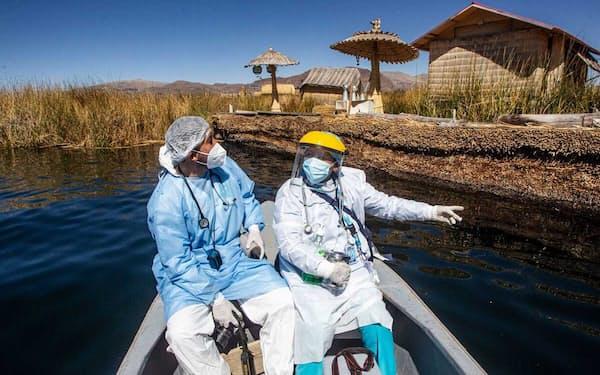 2021年7月7日、ティティカカ湖のウロス島(ペルー南部プーノ)の住民に新型コロナウイルスワクチンを接種しに行くペルーの医療従事者(PHOTOGRAPH BY CARLOS MAMANI, AFP VIA GETTY IMAGES)