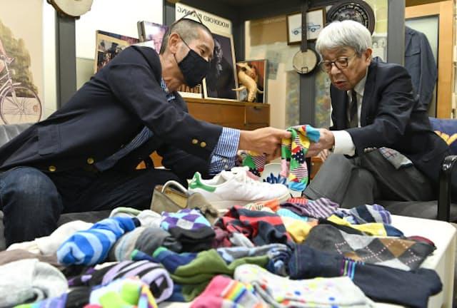 「これはちょっとビジネスには不向きじゃないの?」と靴下を吟味する石津祥介さん(右)。大量の靴下を持ってきてくれた安藤健治さんと靴下選びを楽しんだ(東京都港区の石津事務所)