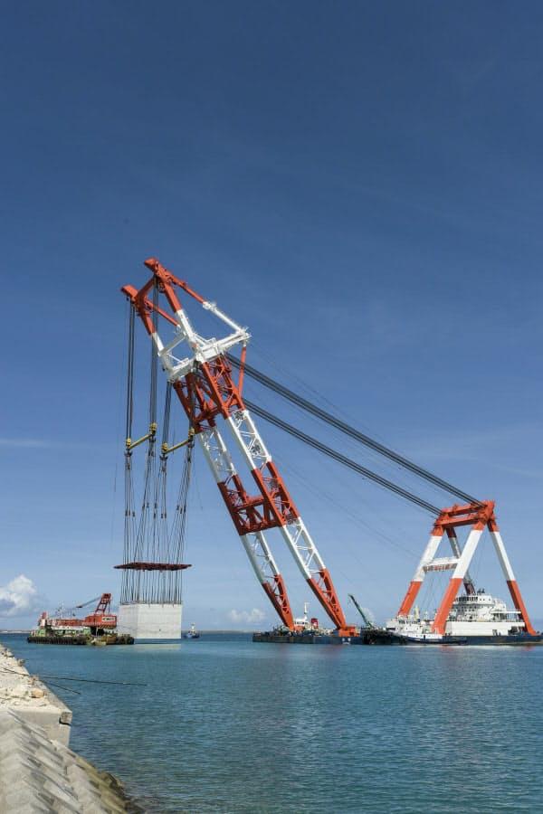 那覇空港に増設する滑走路を埋め立てる際の護岸整備に用いるケーソンを、起重機船で吊り上げているところ(写真:河野哲舟)