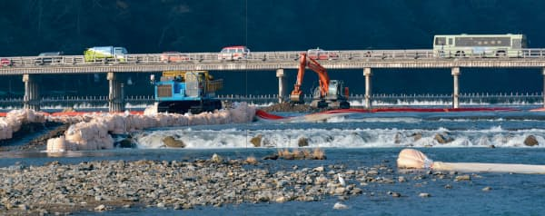 渡月橋付近で掘削した堆積土砂を不整地運搬車で下流に向け搬出する。大型土のうを積んだ部分は6号井堰(写真:大村拓也)
