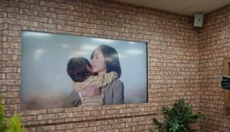 サイボウズ本社。「働くママたちに、よりそうことを。」の動画を画面に表示していた