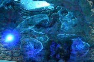 海底エリアに設置された洞窟状の水槽。魚が泳ぐ水槽を下から見上げる。クラゲのペイントや青いライトで幻想的な雰囲気を出した(写真:日経アーキテクチュア)