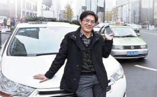 中国・成都で業務用洗濯機の営業職を務める黄永洋さんは、古びたタクシーを横目に毎月、数十人の客を自家用車で運んでいる (写真:町川秀人)