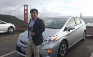 筆者とウーバーで使用している自家用車のトヨタ「Prius」。後ろはサンフランシスコの象徴的存在「金門橋(ゴールデン・ゲート・ブリッジ)」