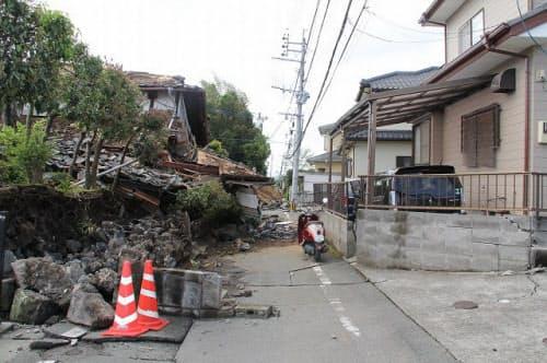 通りの左側は、旧耐震基準と思われる古い住宅が並んで倒壊し、道を塞いでいる。通りの反対側は新耐震基準導入以降と考えられる住宅で、外壁には目立った被害は見られない(写真:日経ホームビルダー)