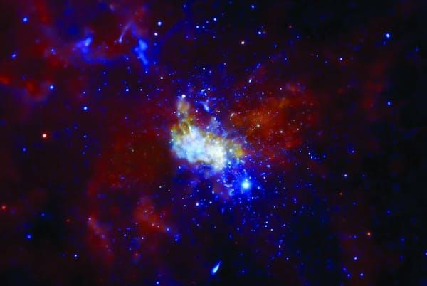 天の川銀河の心臓部にあるブラックホールを囲む荒々しい領域。エックス線はエネルギー量によって色分けされていて、赤が最も弱く、青になるほど強くなる。ブラックホールそのものは、明るい中心部分の一番上に横たわっていて、近隣にある巨星が放出した高温ガスの層の中に埋もれている。チャンドラX線観測衛星で撮影した画像。(NASA/CXC/MIT/F. Baganoff, R. Shcherbakov et al.)