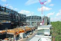 図1 国道20号をまたぎ東京スタジアム(味の素スタジアム)に向かう陸橋から見た武蔵野の森総合スポーツ施設の建設現場。鉄骨鉄筋コンクリート造、鉄骨造(屋根)、一部鉄筋コンクリート造。地下1階、地上4階。左手前がサブアリーナ・プール棟で、奥が五輪会場となるメーンアリーナ棟(写真:日経アーキテクチュア、2015年9月撮影)