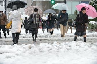 雪が降る中、足元を確かめながら歩く人たち(18日午前、東京都八王子市)