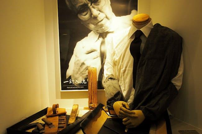 創業者吉田吉蔵氏の作業中の姿を当時の服と道具で再現。腕抜きも愛用のものという