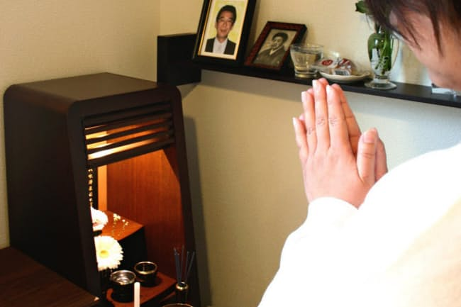 父の位牌に手を合わせる佐藤好美さん。父が最期を過ごした部屋に小さな仏壇を置いた