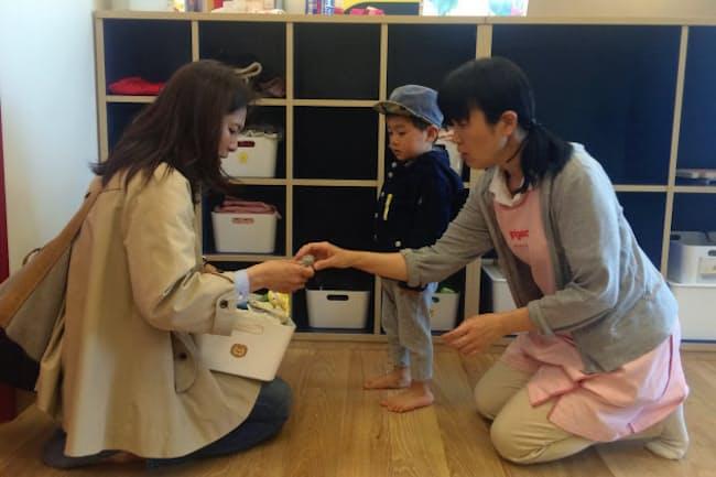 仕事を終えて、勤務先の託児施設に子供を迎えに来た母親(川崎市幸区のFUSO KINDERGARTEN)