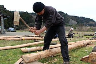 仲間と石斧で木材を削る筆者