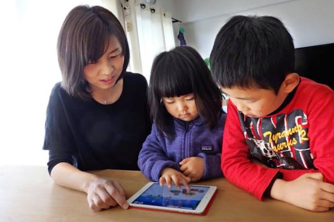 タブレットで電子絵本を楽しむ友広さん親子