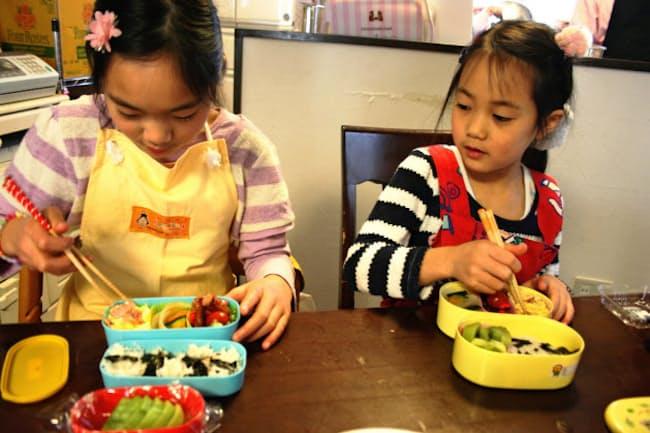 お花見の弁当をつくる阿川さんの長女(左)と次女。ベーコン入りの炒り卵は長女の得意料理