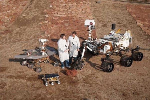NASAの2人の技術者が、米国カリフォルニア州パサデナのジェット推進研究所(JPL)で開発された3世代の火星探査車と記念撮影。火星探査車キュリオシティは「車輪のついた実験室として構想されました」とバサバダ氏。(PHOTOGRAPH BY NASA/JPL-CALTECH )