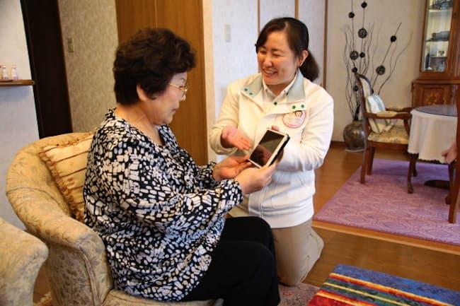 タブレットでその日の業務を利用者に報告するエルケアの高木友美さん(写真右、千葉県船橋市)