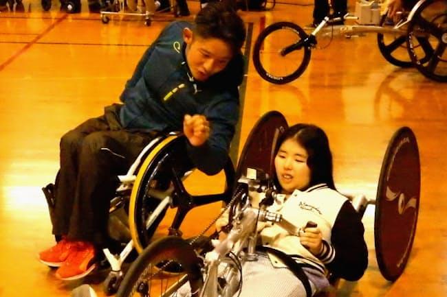 車いすマラソンのトップアスリートから指導を受ける池田恵美さん(右)(東京都立城南特別支援学校提供)