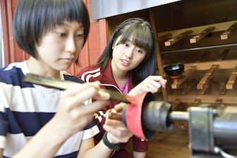 プロの漆塗りを見学するももいろクローバーZ、佐々木彩夏さん(右)