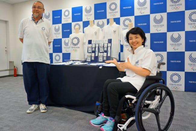 エンブレム入りのTシャツなどを紹介する田口亜希さん(右)