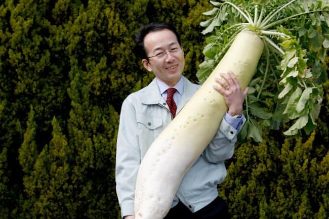 「万田酵素」を使って栽培したジャンボ大根を担ぐ万田発酵の松浦良紀社長
