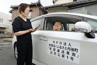 配車依頼するウーバーのアプリが入った端末を持つ女性(左)と「ささえ合い交通」の自家用車(京都府京丹後市)