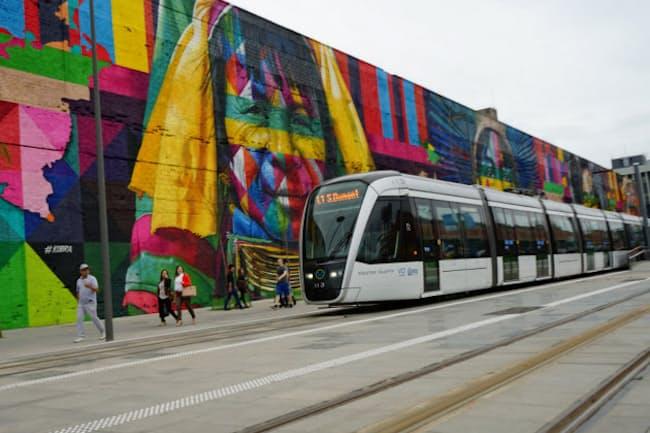 巨大壁画のわきを走り抜けるリオのLRT(写真・山根昭)