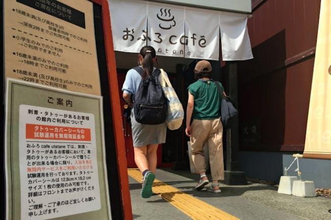 「おふろcafe utatane」では入り口近くでタトゥーを隠すシールの配布を周知している(さいたま市)