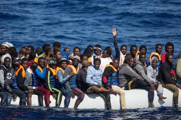 リビアから12カイリ沖の地中海で見つかった全長11メートルのゴムボートには、約150人がひしめき合うように乗っていた。イタリアを目指して海へ出た難民ボートのほとんどは、海上で救助される。無事イタリアまでたどり着いたボートは、これまで1隻もない。(PHOTOGRAPH BY HEREWARD HOLLAND)