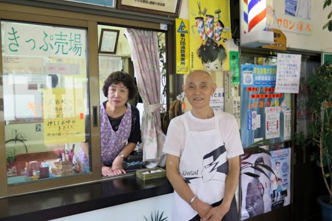 切符売り場の隣に理髪店の入り口がある。塚本久夫さん(右)と朝子さん夫妻