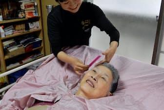 髪をカットしてもらう津山ケイ子さん(東京都北区の自宅)