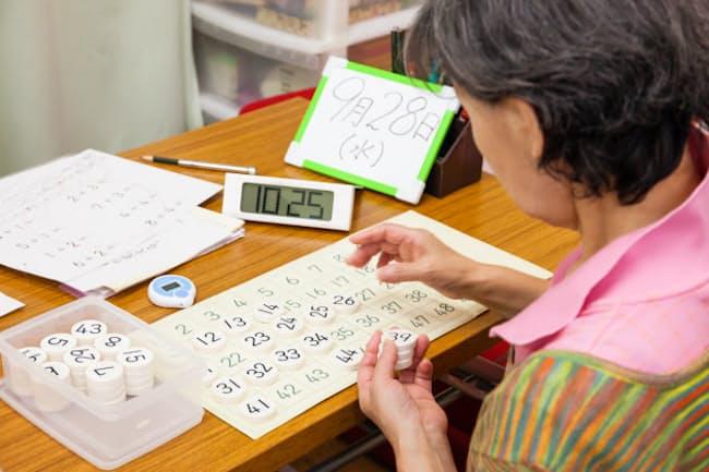 認知症の予防・改善のための学習療法ですうじ盤の作業を行う学習者(アタマの体操教室デイサービスふくろう舎)