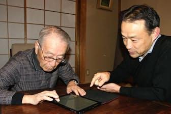 父の松岡正治さんにフェイスブックを手ほどきする長男の正道さん(東京都世田谷区の松岡正治さん宅)