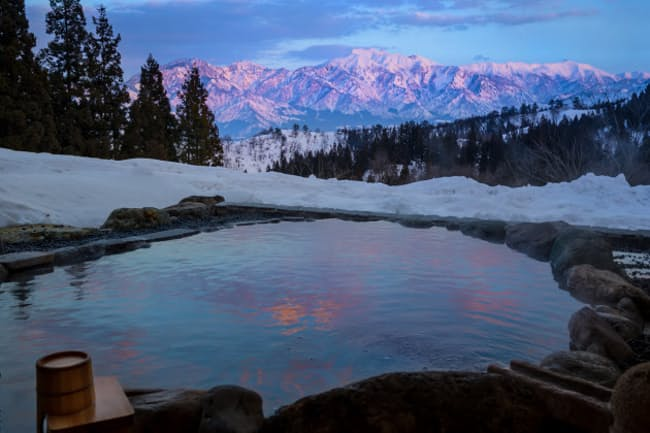 大沢山温泉「里山十帖」の露天風呂から雪を抱いた山々を望む(里山十帖提供)