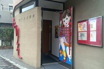 ぬりえ美術館の入り口。扉の表裏にカラフルな服を着た女の子が描かれている