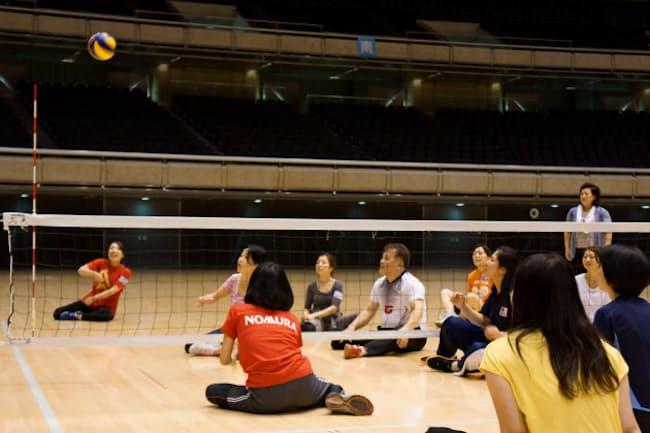 野村ホールディングスは日本パラバレーボール協会の協力を得て、シッティングバレーの体験会を開いた(東京・渋谷の東京体育館)