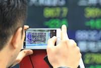 株価ボードを撮影する人