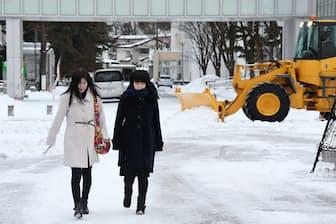 大学入試センター試験を控え、除雪車が作業する秋田大学。雪が積もる構内を会場の下見で受験生(右)が保護者と訪れた(13日午後、秋田市)=共同