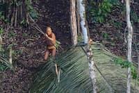 ブラジルのジャングル奥深く、低空飛行するヘリコプターに向かって弓矢を構える孤立部族。(Photograph by Ricardo Stuckert)