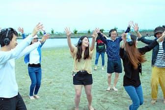 雨宮氏と都内で活動するDJチームの共催で昨夏、川崎市の海浜で開いた「海ロック」の風景。サイレントディスコには20代の女性を中心に、10代から60代まで幅広い世代が集まる。