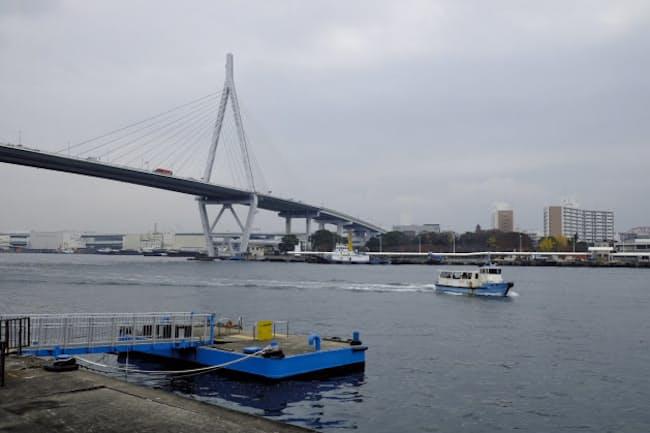 天保山大橋のもと、安治川を渡る天保山渡船。天保山側(向こう側)の乗り場は、橋のたもと近くにある