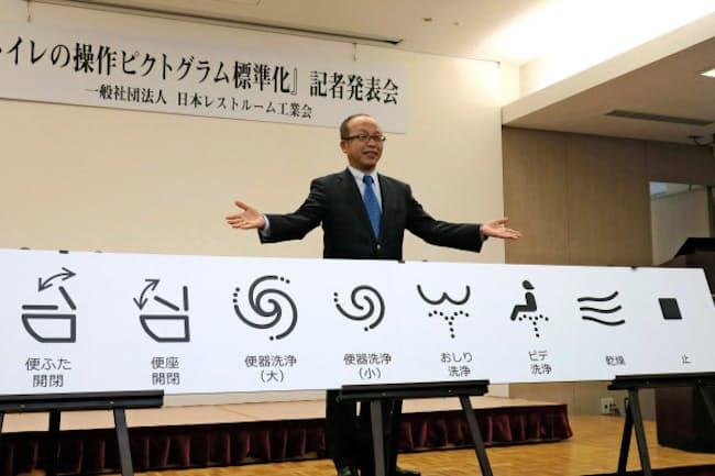 2017年度以降の新製品から統一するトイレの操作ピクトグラムをTOTOの喜多村円社長が披露した