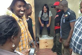 ケニアに設置した無水トイレに立つ山上遊さん(中央)