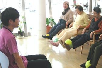 指導員に合わせてストレッチ体操をする利用者(岡山市のデイサービスセンター・アルフィック東川原)