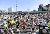 東京マラソンで蔵前橋を走る大勢のランナー。奥は東京スカイツリー(2月26日)=共同