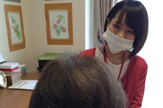 品川成年後見センターの職員(奥)が成年後見人として高齢者の支援にあたる