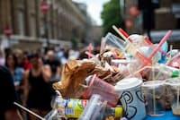 ロンドンのイーストエンド地区で毎週開かれるブリック・レーン・マーケット。ごみ箱に入りきらずにあふれ出たごみの山からは、プラスチック製のストローが何本も突き出ている。(PHOTOGRAPH BY IN PICTURES LTD., CORBIS/GETTY)