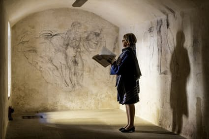 メディチ家礼拝堂の美術館長を務めるモニカ・ビエッティ氏。ミケランジェロの作品集を手に、地下室の壁に描かれたデッサンを調べている。(PHOTOGRAPH BY PAOLO WOODS, NATIONAL GEOGRAPHIC)